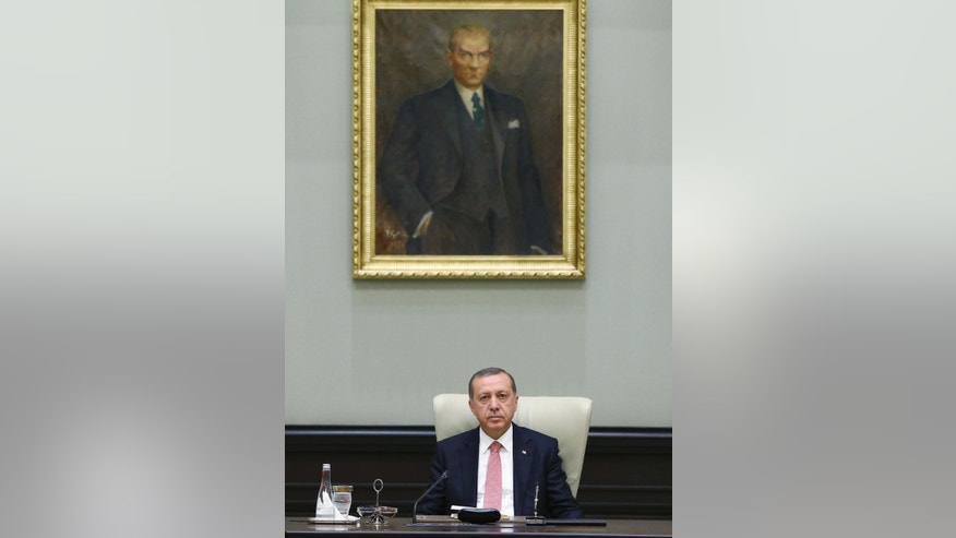 Under a portrait of Turkish Republic founder Mustafa Kemal Ataturk, Turkey's President Recep Tayyip Erdogan chairs the cabinet meeting, in Ankara, Turkey, Monday, July 25, 2016. Turkey on Monday issued warrants for the detention of 42 journalists suspected of links to the alleged organizers of a failed military uprising, intensifying concerns that a sweeping crackdown on alleged coup plotters could target media for any news coverage critical of the government. (Presidential Press Service, Pool via AP)