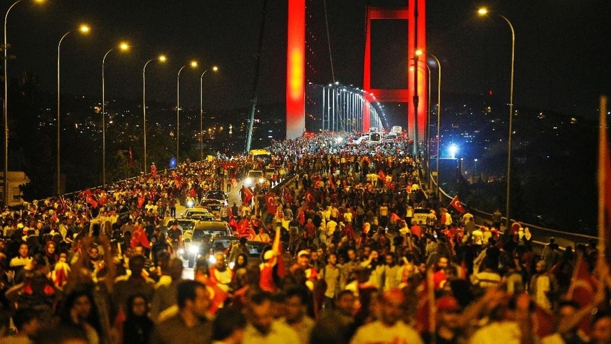 "FILE - In this Thursday, July 21, 2016 file photo, pro-government supporters protest against the attempted coupon Istanbul's iconic Bosporus Bridge. Turkish Prime Minister Binali Yildirim said Monday, July 25, 2016 that Istanbul's Bosporus Bridge will be renamed ""July 15th Martyrs' Bridge"" in honor of civilians who died resisting Turkey's coup attempt. (AP Photo/Emrah Gurel, File)"