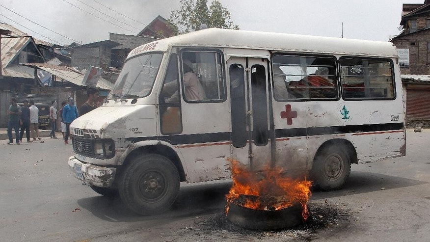 An Ambulance drives past a burning tire put by protesters as a blockade soon after the authorities lift the curfew in Srinagar, Indian-controlled Kashmir, Tuesday, July. 26, 2016. Authorities on Tuesday lifted a curfew in most parts of Indian-controlled Kashmir's main city after a 17-day security lockdown, but shops and businesses remained shut due to a strike called to protest Indian rule in the Himalayan region. (AP Photo/Mukhtar Khan)