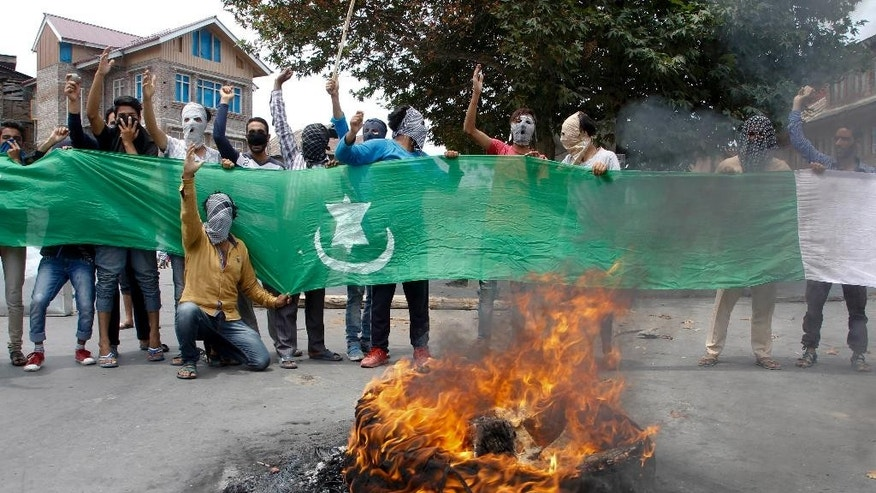 Masked Kashmiri protesters shout slogans displaying the Pakistani flag soon after the authorities lift the curfew in Srinagar, Indian-controlled Kashmir, Tuesday, July. 26, 2016. Authorities on Tuesday lifted a curfew in most parts of Indian-controlled Kashmir's main city after a 17-day security lockdown, but shops and businesses remained shut due to a strike called to protest Indian rule in the Himalayan region. (AP Photo/Mukhtar Khan)