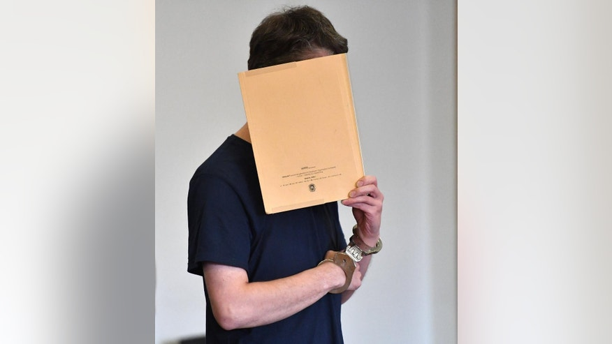 Silvio S. enters the courtroom with a folder in front of his face for the pronouncement of the verdict in the regional court in Potsdam, Germany, Tuesday, July 26, 2016. The court has sentenced the 33-year-old German man to life in prison for the murder of two small boys, one of whom was kidnapped from a refugee registration center. (Ralf Hirschberger/dpa via AP)