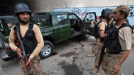 Pakistan army soldiers stand guard next to a damage army vehicle after an attack in Karachi, Pakistan, Tuesday, July 26, 2016. Pakistani police say unidentified gunmen have killed two army soldiers in a hit and run attack in the southern port city of Karachi. (AP Photo/Shakil Adil)
