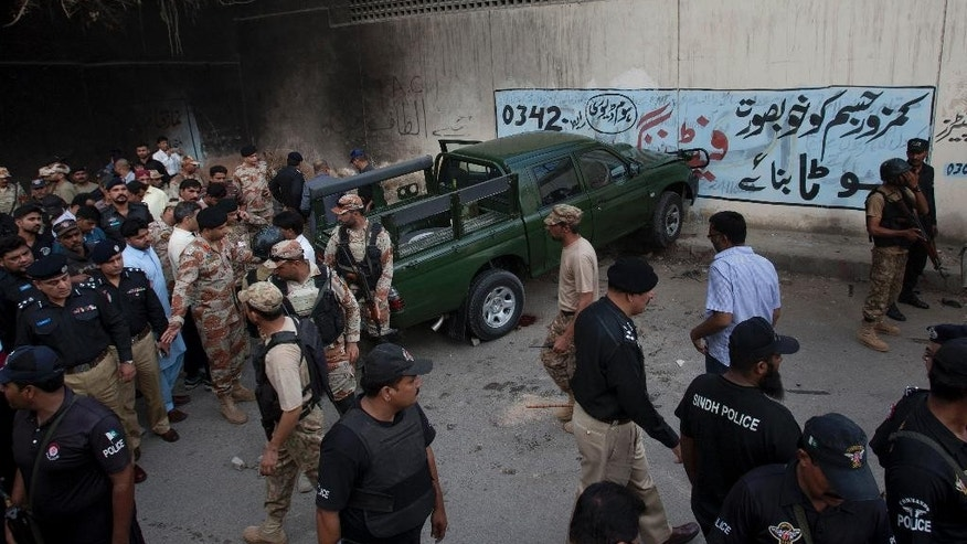 Pakistan army soldiers and police officers gather next to a damaged army vehicle after an attack in Karachi, Pakistan, Tuesday, July 26, 2016. Pakistani police say unidentified gunmen have killed two army soldiers in a hit and run attack in the southern port city of Karachi. (AP Photo/Shakil Adil)