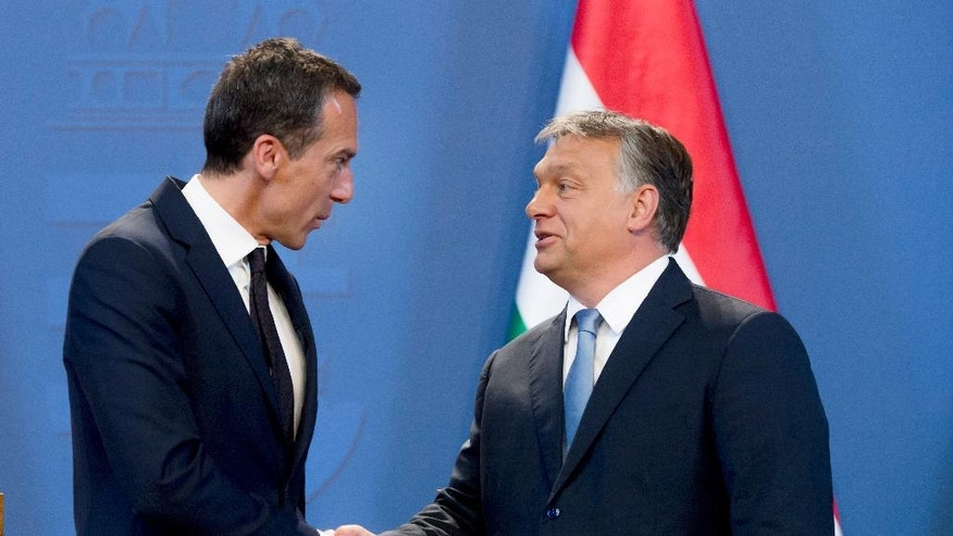 Austrian Chancelor Christian Kern, left, and Hungarian Prime Minister Viktor Orban shake hands after their joint press conference at the Delegation Room of the Parliament in Budapest, Hungary, Tuesday, July 26, 2016. (Szilard Koszticsak/MTI via AP)