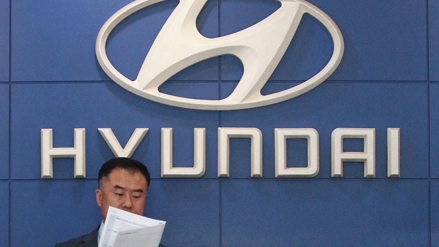 An employee of Hyundai Motor Co. works at the company's showroom in Seoul, South Korea, Tuesday, July 26, 2016. Hyundai Motor Co. says its second-quarter income fell from a year earlier for a tenth straight quarter.(AP Photo/Ahn Young-joon)