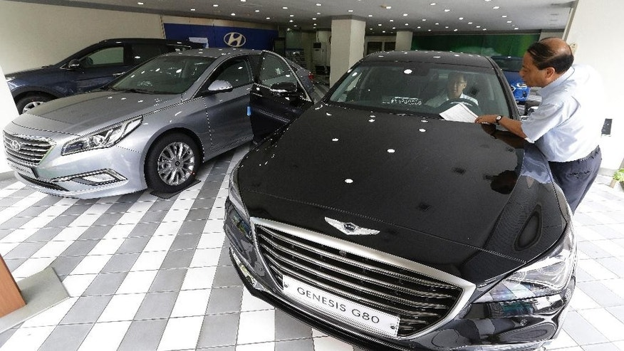 A customer looks at a price of Hyundai Motor Co.'s Genesis G80 at the company's showroom in Seoul, South Korea, Tuesday, July 26, 2016. Hyundai Motor Co. says its second-quarter income fell from a year earlier for a tenth straight quarter.(AP Photo/Ahn Young-joon)