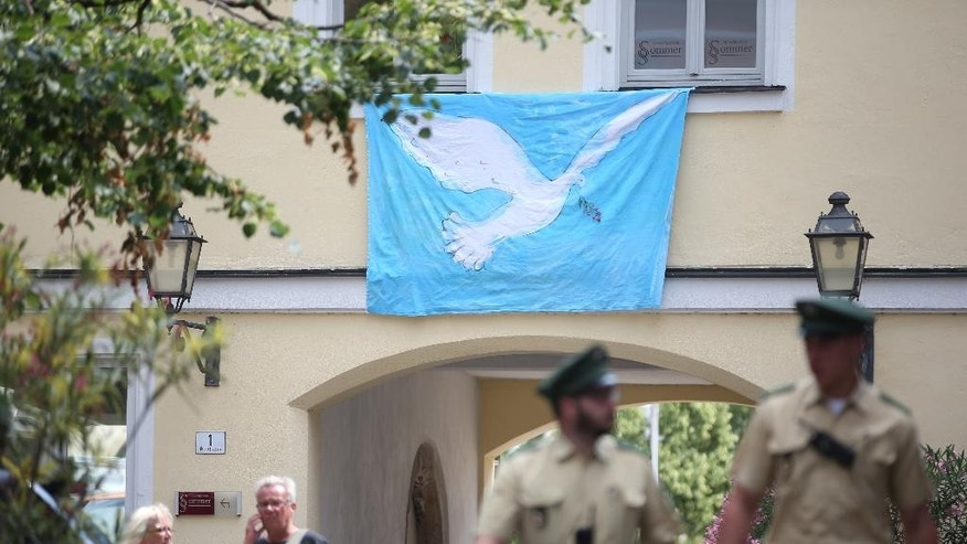 GERMANY OUT - Police officers walk past a wall with a peace dove on a banner at the site of the attack in Ansbach, Germany,Tuesday July 26, 2016.  In the most recent attack, a 27-year-old Syrian asylum-seeker set off a backpack laden with explosives and shrapnel Sunday night after being refused entry to a crowded music festival in the Bavarian city of Ansbach, killing himself and wounding 15 people.  (Daniel Karmann/dpa via AP)