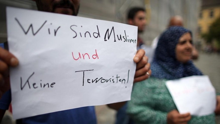 GERMANY OUT - Refugees from Syria stand near the site of the attack and hold up a sign reading  'we are Muslims and not terrorists' in Ansbach, Germany, Tuesday July 26, 2016. In the most recent attack, a 27-year-old Syrian asylum-seeker set off a backpack laden with explosives and shrapnel Sunday night after being refused entry to a crowded music festival in the Bavarian city of Ansbach, killing himself and wounding 15 people.  (Daniel Karmann/dpa via AP)