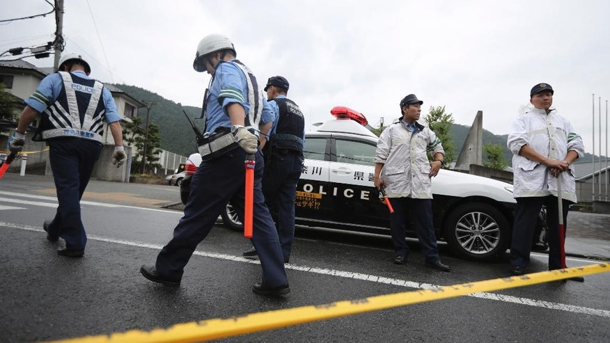 Police officers stand guard at the main gate of Tsukui Yamayuri-en, a facility for the disabled where a number of people were killed and dozens injured in a knife attack in Sagamihara, outside Tokyo Tuesday, July 26, 2016. Police said they responded to a call at about 2:30 a.m. from an employee saying something horrible was happening at the facility in the city of Sagamihara, 50 kilometers (30 miles) west of Tokyo. A man turned himself in at a police station about two hours later, police said. (AP Photo/Eugene Hoshiko)
