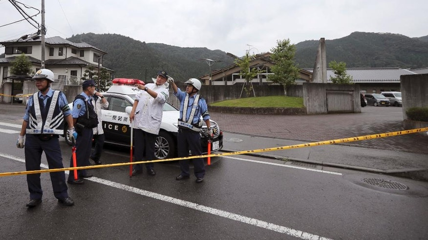 Police officers stand guard in front of the main gate of the Tsukui Yamayuri-en, a facility for the disabled where a number of people were killed and dozens injured in a knife attack in Sagamihara, outside Tokyo Tuesday, July 26, 2016. Police said they responded to a call at about 2:30 a.m. from an employee saying something horrible was happening at the facility in the city of Sagamihara, 50 kilometers (30 miles) west of Tokyo. A man turned himself in at a police station about two hours later, police said. (AP Photo/Eugene Hoshiko)