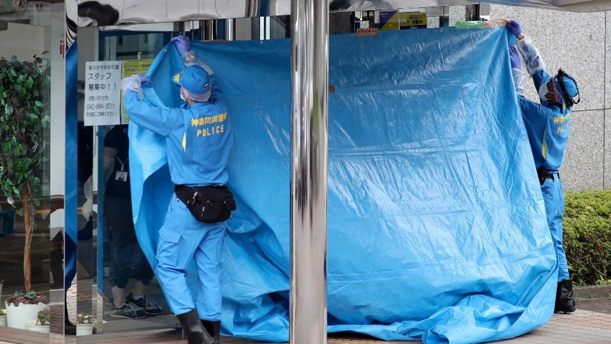 Police investigators cover the entrance of the Tsukui Yamayuri-en, a facility for the disabled where a number of people were killed and dozens injured in a knife attack, with a blue sheet in Sagamihara, outside Tokyo Tuesday, July 26, 2016. Police said they responded to a call at about 2:30 a.m. from an employee saying something horrible was happening at the facility in the city of Sagamihara, 50 kilometers (30 miles) west of Tokyo. A man turned himself in at a police station about two hours later, police said. (AP Photo/Eugene Hoshiko)