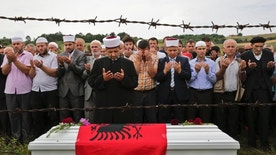 An Imam holds a prayer near the coffin draped with an Albanian flag of Diamant Zabergja 21, during his funeral ceremony in the village of Ropice, Kosovo on Tuesday, July 27, 2016. Zabergia is one of the victims of the Olympia shopping center in Munich, where a shooting took place leaving nine people dead four days ago. Three ethnic Albanians, two women and a man, were among the nine people killed. (AP Photo/Visar Kryeziu)