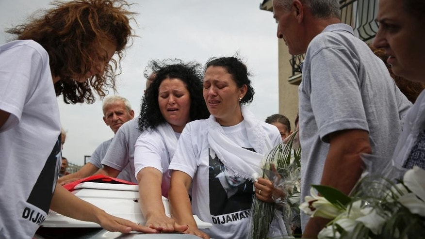 Family members mourn over the coffin of Diamant Zabergja, 21, one of the victims of the Olympia shopping centre in Munich, during his funeral ceremony in the village of Ropice, Kosovo, Tuesday, July 26, 2016. Three ethnic Albanians, two women and a man, were among the nine people killed by a gunman in Munich four days ago. (AP Photo/Visar Kryeziu)