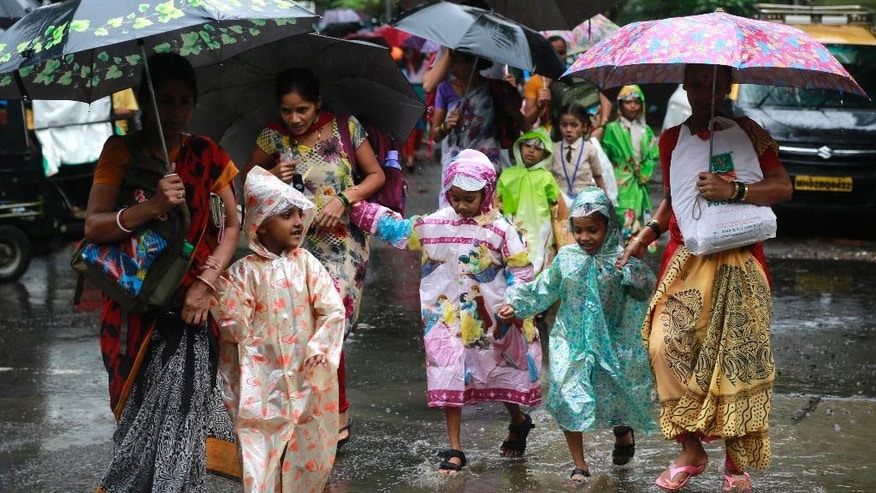 Mothers walk with their children wearing raincoats as they cross a flooded road in Mumbai, India, Tuesday, July 26, 2016. The monsoon rains usually hit India from June to September. (AP Photo/Rafiq Maqbool)