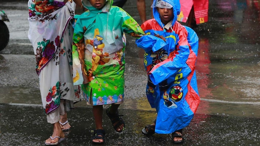 Children return from school wearing colorful raincoats in the rain in Mumbai, India, Tuesday, July 26, 2016. The monsoon rains usually arrive in India from June to September. (AP Photo/Rafiq Maqbool)