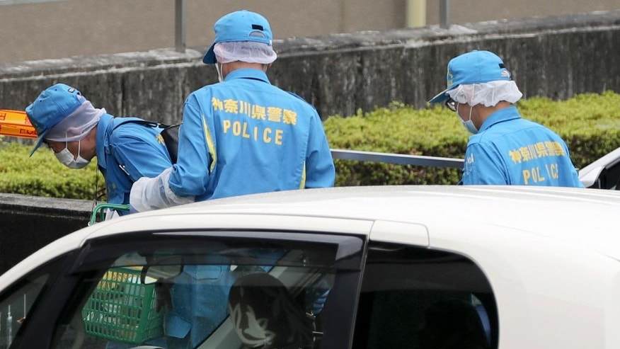 Police investigators check at Tsukui Yamayuri-en, a facility for the handicapped where a number of people were killed and dozens injured in a knife attack in Sagamihara, outside Tokyo Tuesday, July 26, 2016. (AP Photo/Eugene Hoshiko)