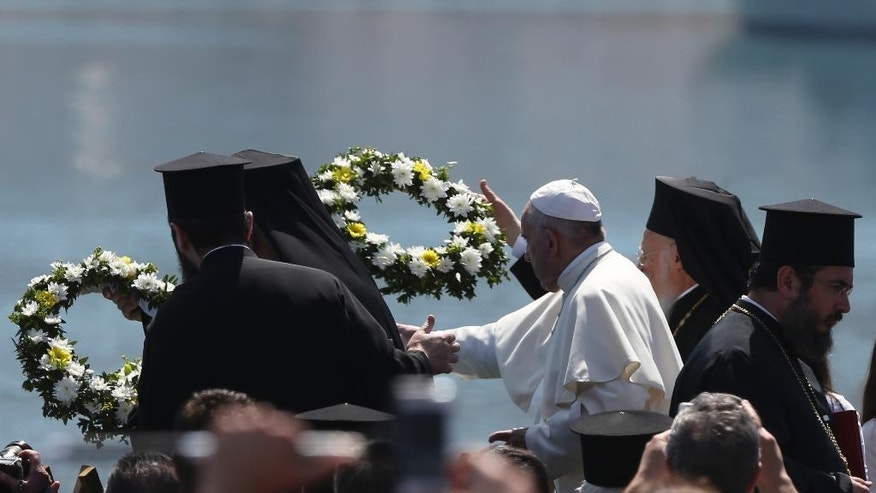 FILE -- In this April 16 2016 file photo, Pope Francis, center, flanked by Ecumenical Patriarch Bartholomew I, spiritual leader of the world's Orthodox Christians, left, and Archbishop of Athens and All Greece Ieronymos II, head of the Church of Greece, lay wreaths of flowers on the Greek island of Lesbos, Saturday April 16, 2016. The pontiff's advocacy for refugee rights faces a diplomatic test Wednesday when he begins a five-day visit to Poland, where a populist government has slammed the door on most asylum seekers. (AP Photo/Petros Giannakouris)