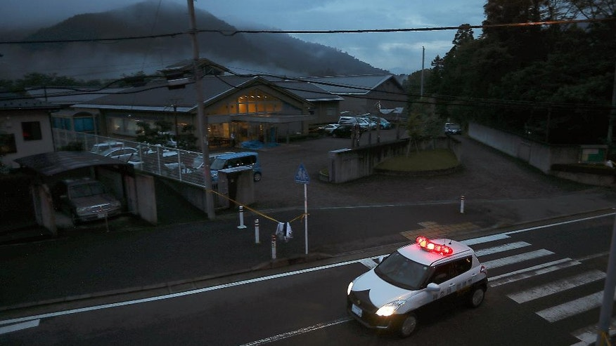 A police car patrols at night in front of the Tsukui Yamayuri-en, a facility for the mentally disables where a number of people were killed and dozens injured in a knife attack in Sagamihara, outside Tokyo Tuesday, July 26, 2016. A young Japanese man went on a stabbing rampage Tuesday at the facility where he had been fired, officials said, killing 19 people months after he gave a letter to Parliament outlining the bloody plan and saying all disabled people should be put to death. (AP Photo/Eugene Hoshiko)