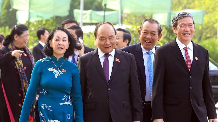 FILE - In this Wednesday, July 20, 2016 file photo, Vietnam's new Prime Minister Nguyen Xuan Phuc, second left, walks with Vietnamese Communist Party Central Committee's Mass Mobilization Chief Truong Thi Mai, left, Chief Justice of the Supreme People's Court Truong Hoa Binh, second right, and Communist Party's Standing Secretary of Secretariat of the Central Committee Dinh The Huynh to the opening session of the 14th National Assembly in Hanoi, Vietnam. Phuc vowed to defend the country's sovereignty in the South China Sea as he was re-elected Tuesday, July 26 by the rubber-stamp National Assembly. (AP Photo/Hau Dinh, File)