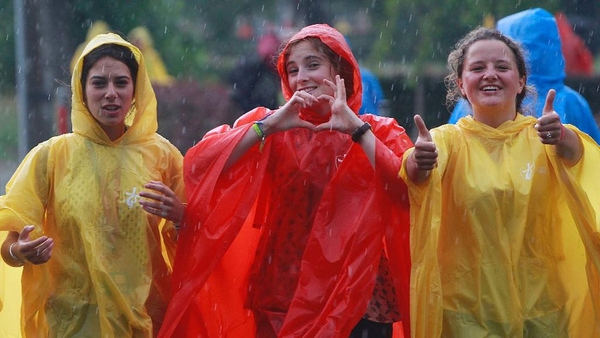 Young women from France are among the dozens of thousands of young people from around the globe walking in thunderstorm to the site of a Catholic Mass in the Blonia green in Krakow, Poland, Tuesday, July 26, 2016 that will officially open the World Youth Day, a major gathering of Catholics that will be joined by Pope Francis on Wednesday. (AP Photo/Czarek Sokolowski)