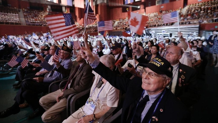 Foreign veterans of the Korean War and their family members wave their national flags during a commemorative ceremony marking the 63rd anniversary of the Armistice Agreement and UN Forces Participation in the Korean War in Seoul, South Korea, Wednesday, July 27, 2016. South Korea is accusing rival North Korea of floating propaganda leaflets via a river in the first such incident. (AP Photo/Ahn Young-joon)