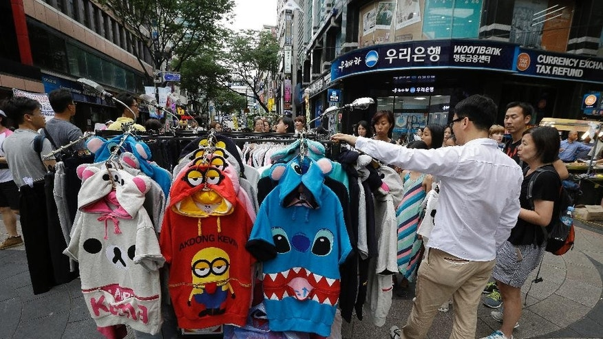 Customers look at clothes at a shopping district in Seoul, South Korea, Tuesday, July 26, 2016. South Korea's economic growth has improved during the second quarter thanks to stronger private consumption and increased housing construction. (AP Photo/Ahn Young-joon)
