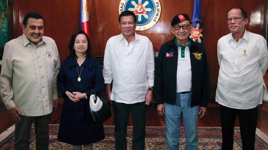 In this handout photo released by the Malacanang Presidential Communications Office, Philippine President Rodrigo R. Duterte, center, poses with, from left, former presidents Joseph E. Estrada, Gloria Macapagal-Arroyo, Fidel V. Ramos and Benigno S. Aquino III before convening for the National Security Council Meeting at the the Malacanang presidential palace on Wednesday, July 27, 2016. The new Philippine leader has gathered four past presidents, most of whom have been politically at odds with one another, to discuss a unifying worry: their country's territorial disputes with China. (AP Photo/Rey Baniquet, Malacanang Presidential Communications Office, HO)