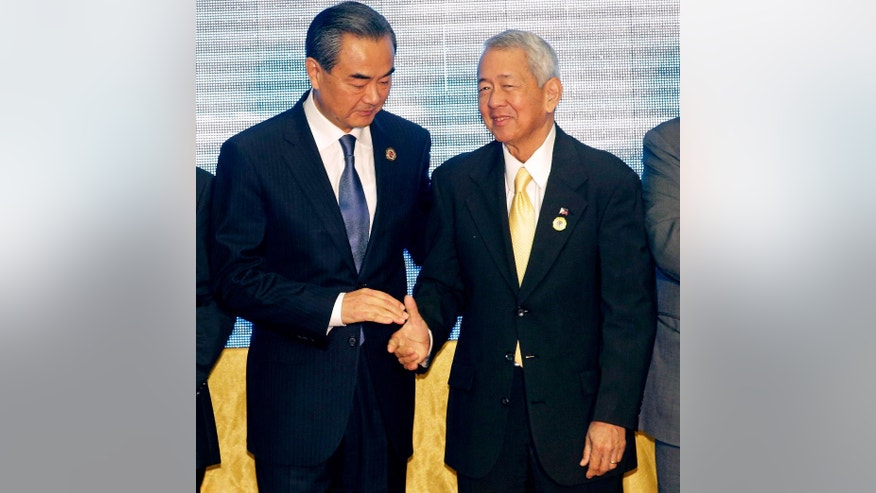 FILE - In this July 26, 2016, file photo, China's Foreign Minister Wang Yi, left, stands with Philippines Foreign Minister Perfecto Yasay Jr. after they pose for a photo during the Association of Southeast Asian Nations (ASEAN) Foreign Ministers' Meeting in Vientiane, Laos. Despite the Philippines taking on China in a territorial dispute in the South China Sea and winning big, other Southeast Asian nations with similar disputes who attended this week's meetings are apparently backing down from Beijing. (AP photo/Sakchai Lalit)