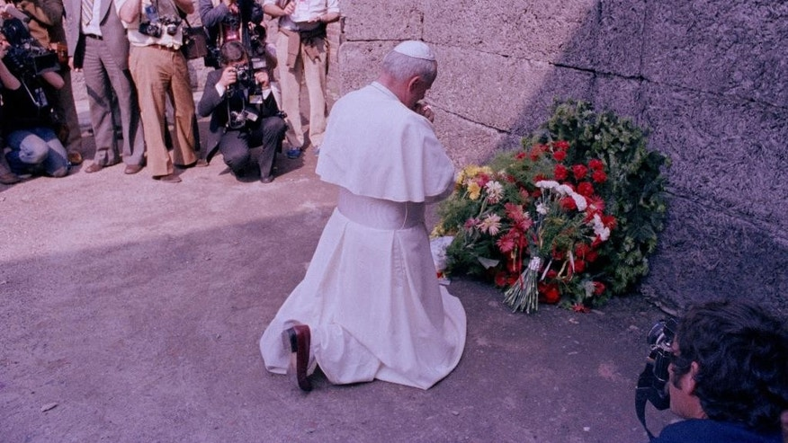 FILE -- In this June 7, 1979 file photo Pope John Paul II prays in front of the death wall at the former Nazi concentration camp Auschwitz in Oswiecim, Poland. Pope Francis will also visit Auschwitz-Birkenau during his forthcoming pilgrimage to Poland, as his predecessors John Paul II and Benedict XVI did. (AP Photo/file)