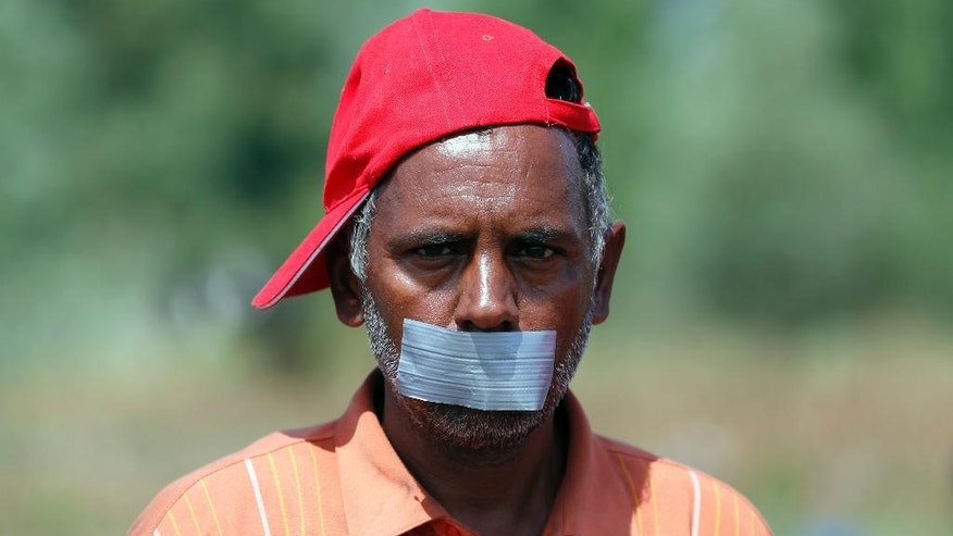 A man tapes his mouth as he protests at a makeshift camp for migrants in Horgos, Serbia, meters away from the border with Hungary, Wednesday, July 27, 2016. Some one hundred men and boys, mostly from Afghanistan and Pakistan, have been protesting Europe's migrant policies for several days now, staging a protest march to Serbia's border with EU-member Hungary where they sat down in a dusty field, without any facilities and accepting only water from humanitarian groups.(AP Photo/Darko Vojinovic)