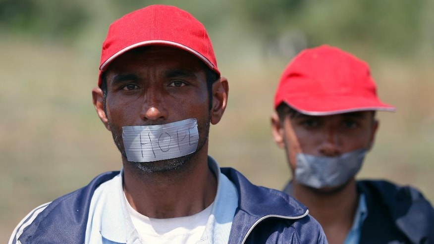 Migrants tape their mouths as they stage a protest at a makeshift camp for migrants in Horgos, Serbia, meters away from the border with Hungary, Wednesday, July 27, 2016. Some one hundred men and boys, mostly from Afghanistan and Pakistan, have been protesting Europe's migrant policies for several days now, staging a protest march to Serbia's border with EU-member Hungary where they sat down in a dusty field, without any facilities and accepting only water from humanitarian groups. (AP Photo/Darko Vojinovic)