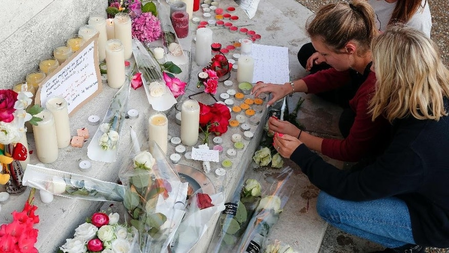 Flowers, candles and messages are placed on the city hall entrance closed to the home of Father Jacques Hamel after he was killed during an attack in a church in Saint-Etienne-du-Rouvray, Normandy, France, Tuesday, July 26, 2016. Two attackers invaded a church Tuesday during morning Mass near the Normandy city of Rouen, killing an 84-year-old priest by slitting his throat and taking hostages before being shot and killed by police, French officials said. (AP Photo/Francois Mori)