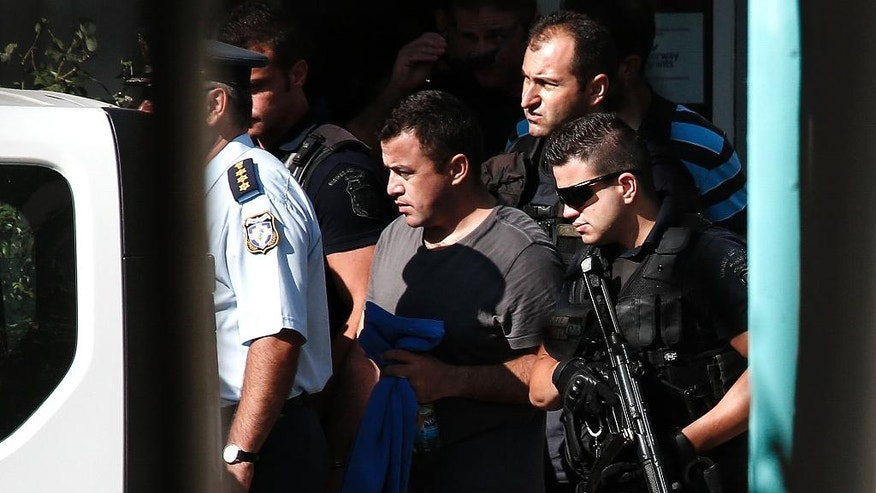 A Turkish military officer, center, is escorted by policemen as he leaves a building of the Greek Asylum Service in Athens, Wednesday, July 27, 2016. Two of the eight Turkish military officers who are seeking asylum in Greece after a failed military coup, appeared in the service and took a postponement for their interview for August 19. (AP Photo/Yorgos Karahalis)