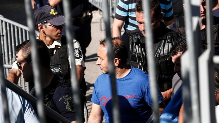 A Turkish military officer, center, is escorted by policemen as he leaves a building of the Greek Asylum Service in Athens, Wednesday, July 27, 2016. Two of the eight Turkish military officers who are seeking asylum in Greece after a failed military coup appeared in the service and took a postponement for their interview for August 19. (AP Photo/Yorgos Karahalis)
