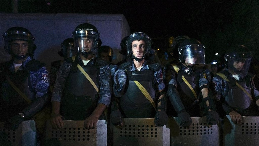 Riot police secure a police station, which is being hold by an armed group, in Yerevan, Armenia, early Wednesday, July 27, 2016. A spokesman for Armenia's police says two of the gunmen who have been holding a police station in the capital for more than a week have surrendered after an exchange of gunfire. Police spokesman Ashot Arahonyan says on Facebook that the gunfire began before dawn on Wednesday. (Vahan Stepanyan/PAN Photo via AP)