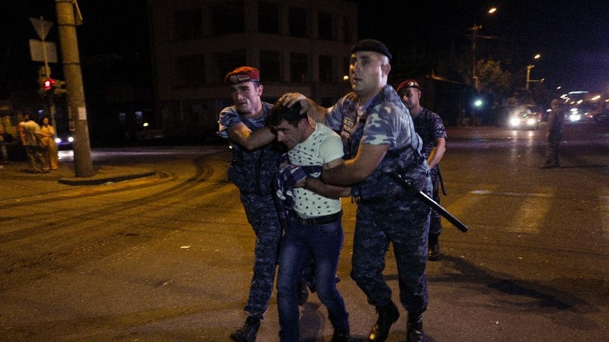Police officers detain a supporter of the armed group who have been holding a police station in Yerevan, Armenia, early Wednesday, July 27, 2016. A spokesman for Armenia's police says two of the gunmen who have been holding a police station in the capital for more than a week have surrendered after an exchange of gunfire. Police spokesman Ashot Arahonyan says on Facebook that the gunfire began before dawn on Wednesday. (Vahan Stepanyan/PAN Photo via AP)