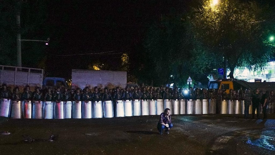 Riot police secure a police station, which is being held by an armed group, in Yerevan, Armenia, early Wednesday, July 27, 2016. A spokesman for Armenia's police says two of the gunmen who have been holding a police station in the capital for more than a week have surrendered after an exchange of gunfire. Police spokesman Ashot Arahonyan says on Facebook that the gunfire began before dawn on Wednesday. (Vahan Stepanyan/PAN Photo via AP)