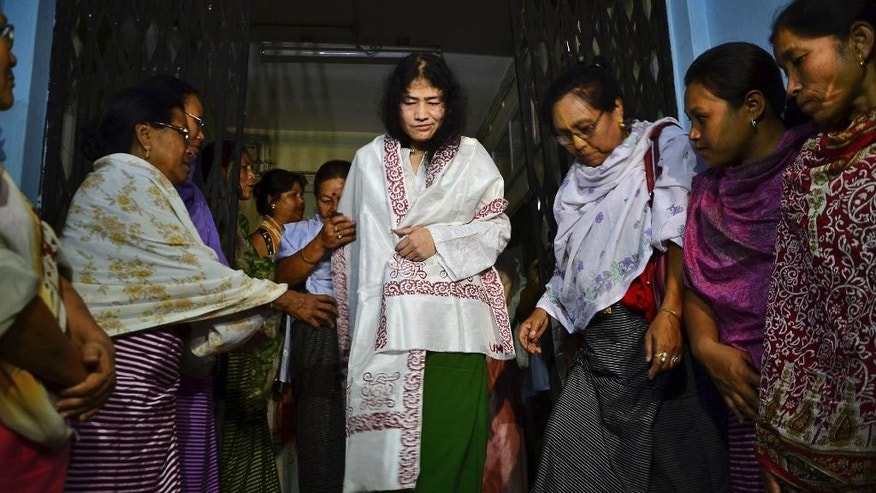 FILE - In this Wednesday, Aug. 20, 2014 file photo, Irom Sharmila, center, walks out of a security ward after her release in Porompal district, in Imphal, India. The frail activist who has been on a hunger strike for nearly 16 years to protest alleged brutality by India's military told a court on Tuesday, July 26, 2016, that she'll give up her fast on Aug. 9 and stand as an independent candidate in elections early next year. Sharmila has not eaten voluntarily since November 2000, when she began her protest against an Indian law that suspends many human rights protections in areas of conflict. She was arrested three days after starting her fast on charges of attempting suicide and has since been force fed through a tube in her nose. (AP Photo/Bullu Raj, File)