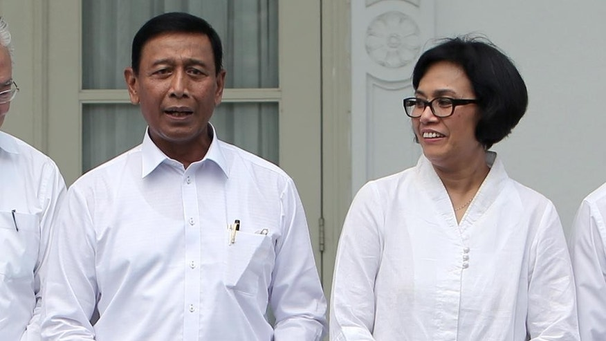 "Indonesia's new Finance Minister Sri Mulyani Indrawati, right, and Coordinating Minister for Legal, Security and Politics Wiranto prepare for a group photo during the announcement of the new cabinet ministers at Merdeka Palace in Jakarta, Indonesia, Wednesday, July 27, 2016. Indonesian President Joko ""Jokowi"" Widodo announced a new Cabinet line-up on Wednesday that returns a reformist to the Finance Ministry and puts a former head of the military in charge of security. (AP Photo/Tatan Syuflana)"