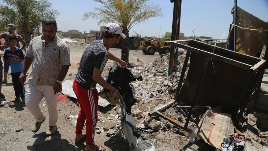 Civilians clean the scene of a suicide bombing at the northern neighborhood of Shula, Baghdad, Iraq, Wednesday, July 27, 2016. A suicide bomber targeted a police checkpoint in a Shiite neighborhood in Baghdad on Wednesday, killing several people. (AP Photo/Karim Kadim)