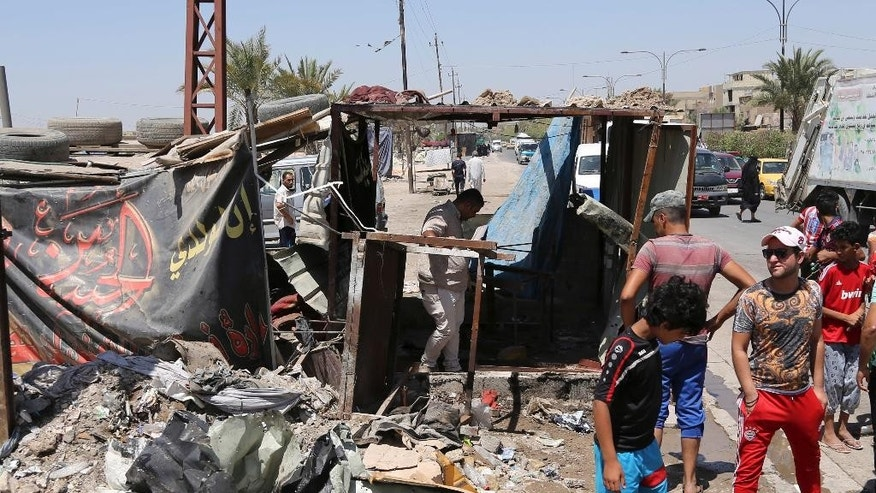 Civilians gather at the scene of a suicide bombing at the northern neighborhood of Shula, Baghdad, Iraq, Wednesday, July 27, 2016. A suicide bomber targeted a police checkpoint in a Shiite neighborhood in Baghdad on Wednesday, killing at least six people. (AP Photo/Karim Kadim)