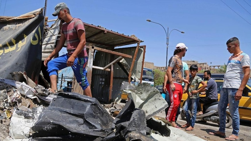 Civilians gather at the scene of a suicide bombing at the northern neighborhood of Shula, Baghdad, Iraq, Wednesday, July 27, 2016. A suicide bomber targeted a police checkpoint in a Shiite neighborhood in Baghdad on Wednesday, killing at several people. (AP Photo/Karim Kadim)
