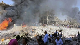 In this photo released by the Syrian official news agency SANA, Syrians gather at the scene where twin bombings struck Kurdish town of Qamishli, Syria, Wednesday, July 27, 2016. Twin bombings struck a crowd in a predominantly Kurdish town in northern Syria on Wednesday, killing 44 people and wounding dozens more, Syria's state-run news agency and Kurdish media reported. (SANA via AP)