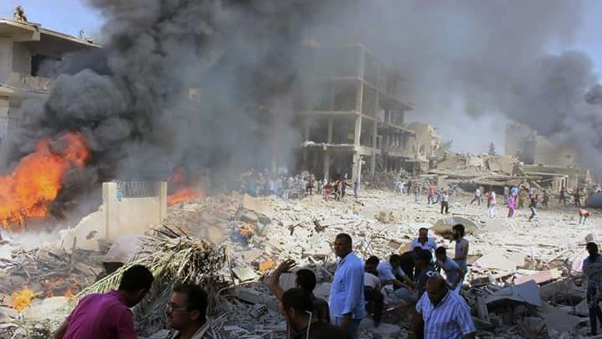 Syrians gather at the scene where twin bombings struck Kurdish town of Qamishli, Syria.