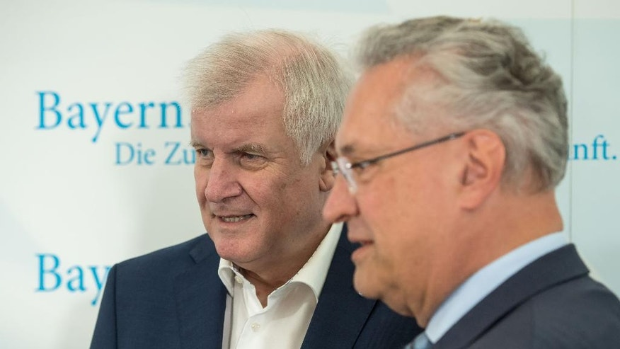 GERMANY OUT - Bavarian governor Horst Seehofer, left, and Bavaria's Interior Minister,  Joachim Herrmann arrive for a meeting of the Bavarian cabinet ,in Gmund, Germany, Tuesday, July 26, 2016.   In the most recent attack, a 27-year-old Syrian asylum-seeker set off a backpack laden with explosives and shrapnel Sunday night after being refused entry to a crowded music festival in the Bavarian city of Ansbach, killing himself and wounding 15 people.   ( Peter Kneffel/dpa via AP)
