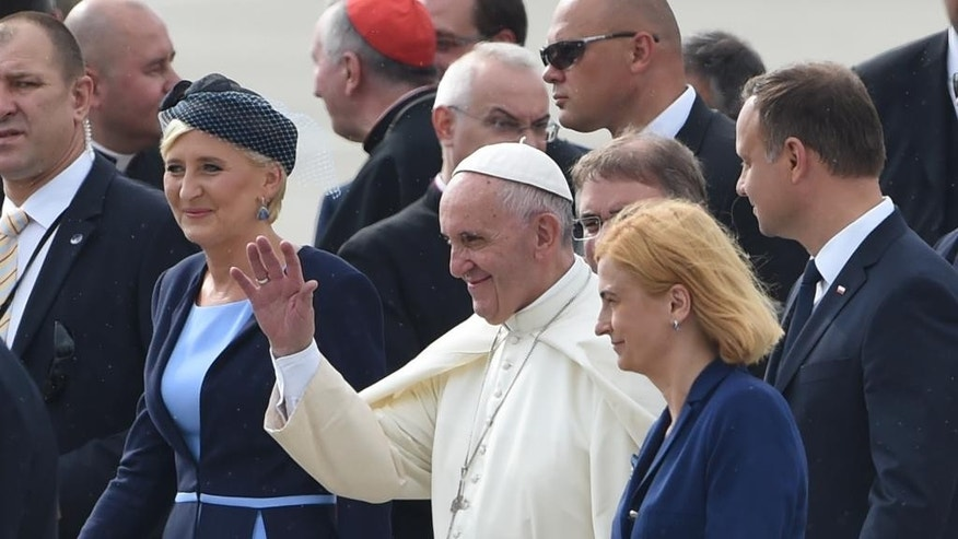 Pope Francis greets faithful as he walks with Polish President Andrzej Duda, right, and his wife Agata Kornhauser Duda, left, after the welcome ceremony at the military airport in Krakow, Poland, Wednesday, July 27, 2016. (AP Photo/Alik Keplicz)