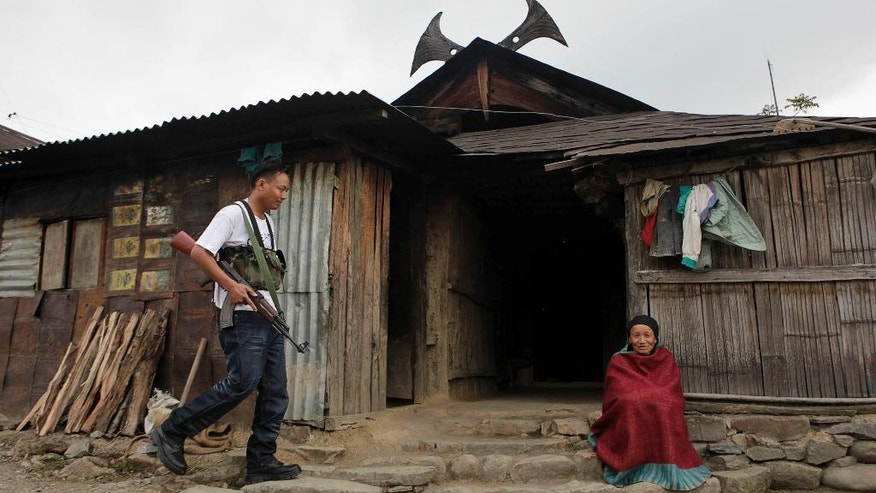 FILE – In this May 5, 2010 file photo, an armed cadre of the National Socialist Council of Nagaland (NSCN-IM), left, walks past an elderly woman sitting outside a traditional Naga hut, during a visit by the NSCN-IM General-Secretary Thuingaleng Muivah, at Viswema village, about 25 kilometers (16 miles) south of Kohima, capital of the northeastern Indian state of Nagaland. In India's remote northeast, government forces battle dozens of ethnic insurgent groups who push a welter of demands ranging from independent homelands to maximum autonomy within India. The most prominent of those conflicts, that of the Naga people, has been on the boil since the mid-1950s. (AP Photo/Anupam Nath, File)
