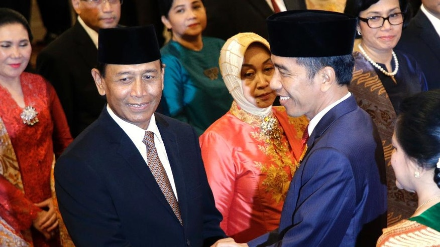 Indonesia's President Joko Widodo, right, congratulates the Coordinating Minister for Legal, Politics and Security Affairs Wiranto after the inauguration ceremony for the new cabinet members at the State Palace in Jakarta, Wednesday, July 27, 2016. Widodo announced a new Cabinet on Wednesday that puts the retired general linked to human rights abuses in charge of security and returns a popular reformist to the finance ministry. (AP Photo/Tatan Syuflana)
