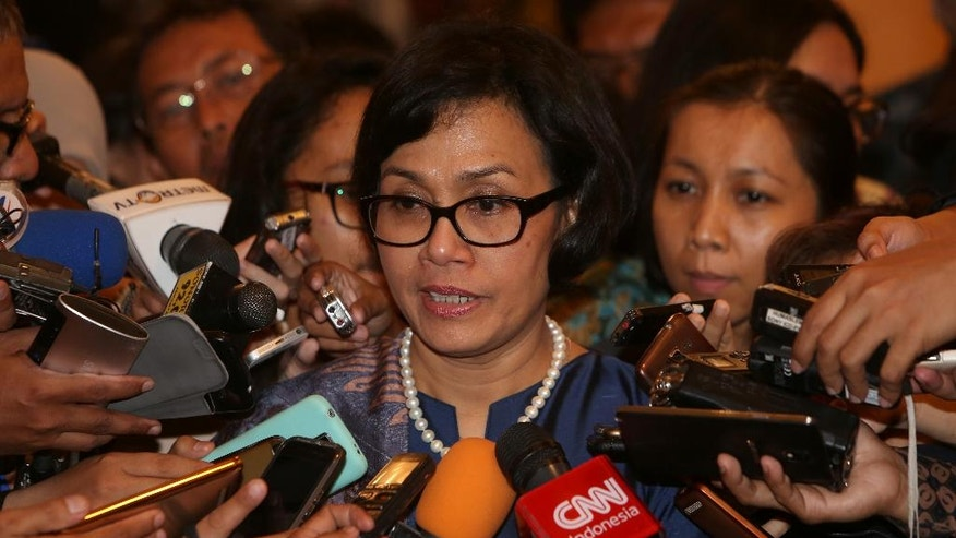 """Indonesia's new Finance Minister Sri Mulyani Indrawati speaks to the media after her inauguration ceremony at the State Palace in Jakarta, Wednesday, July 27, 2016. Indonesian President Joko """"Jokowi"""" Widodo announced a new Cabinet on Wednesday that puts a retired general linked to human rights abuses in charge of security and returns the popular reformist to the finance ministry. (AP Photo/Tatan Syuflana)"""