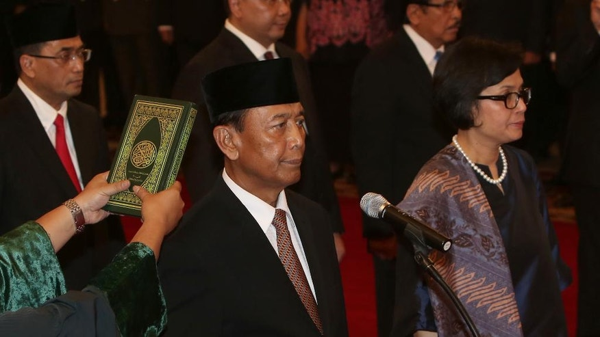 """Indonesia's newly appointed Coordinating Minister for Legal, Politics and Security Affairs Wiranto, left, and Finance Minister Sri Mulyani Indrawati, right, are sworn in during the inauguration ceremony for the new cabinet members at the State Palace in Jakarta, Wednesday, July 27, 2016. Indonesian President Joko """"Jokowi"""" Widodo announced a new Cabinet on Wednesday that puts the retired general linked to human rights abuses in charge of security and returns the popular reformist to the finance ministry. (AP Photo/Tatan Syuflana)"""